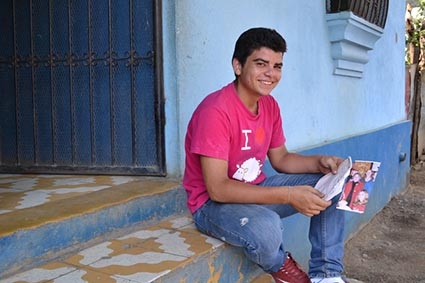 young man sitting on step holding a photo