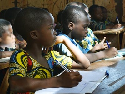 children sitting at tables in classroom