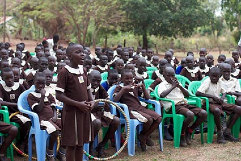 young girl standing and speaking in front of group of children
