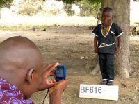 Man taking a picture of a child standing in front of a tree with a sign in front of his feet