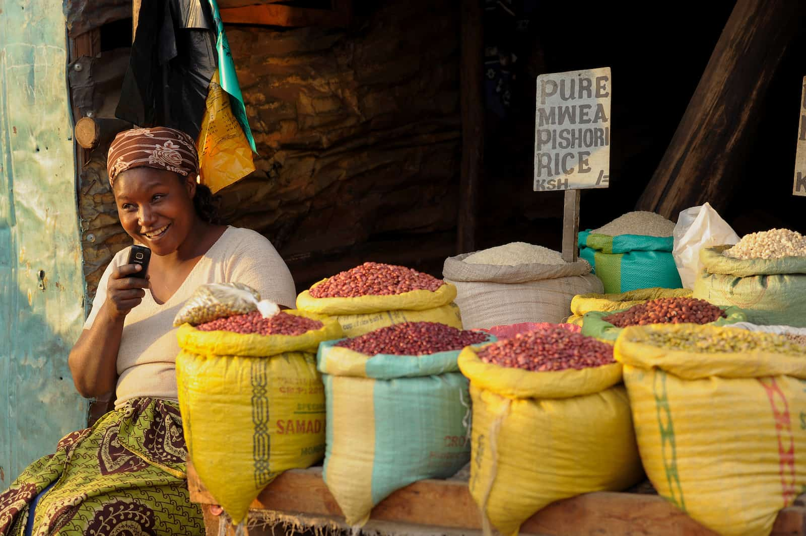 A woman selling beans on a street in Kibera, where some people go for poverty tourism.