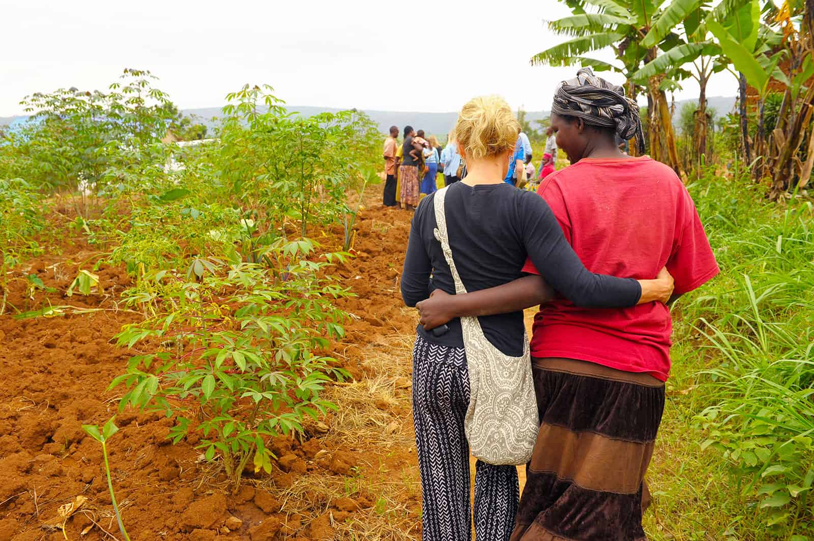 Two women walk down a dirt path together with their arms around one another.