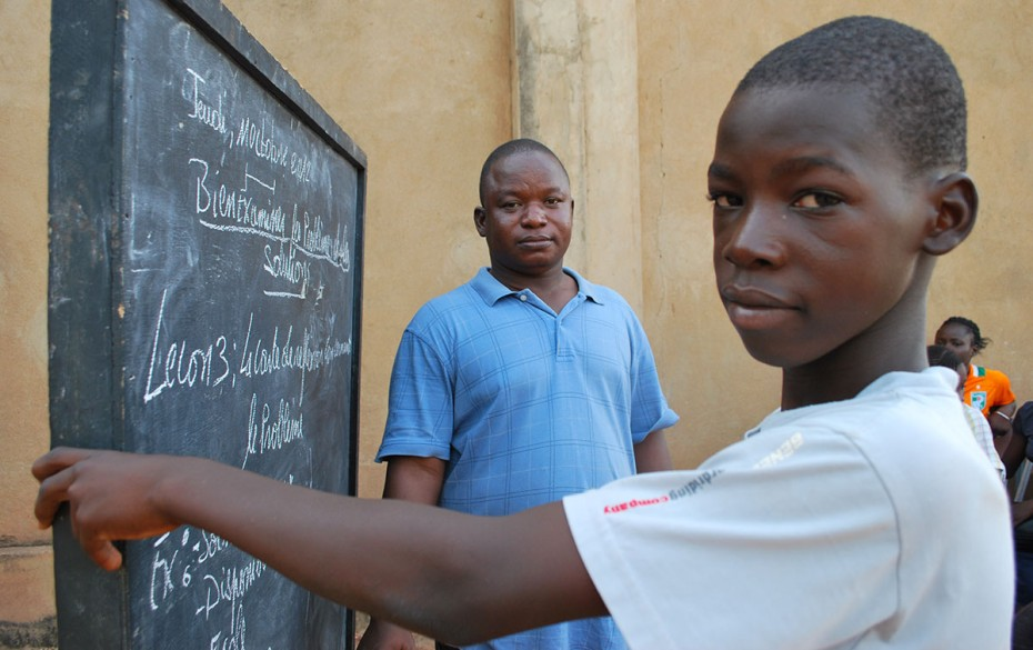 a boy standing in front of a chalkboard