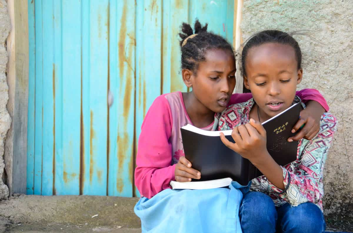 Two girls wearing pink tops and denim bottoms huddle together to read the Bible.