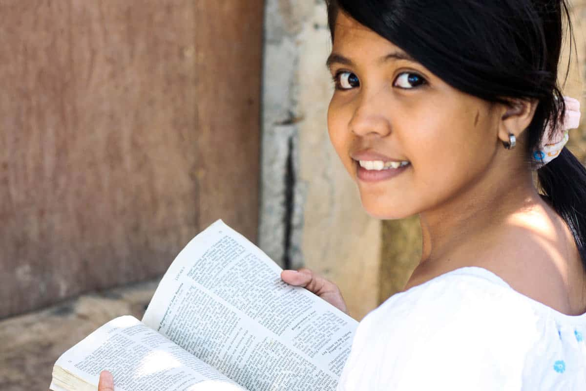 a girl holding an open Bible smiles at the camera. Her dark hair is in a ponytail, and she is wearing a white shirt.