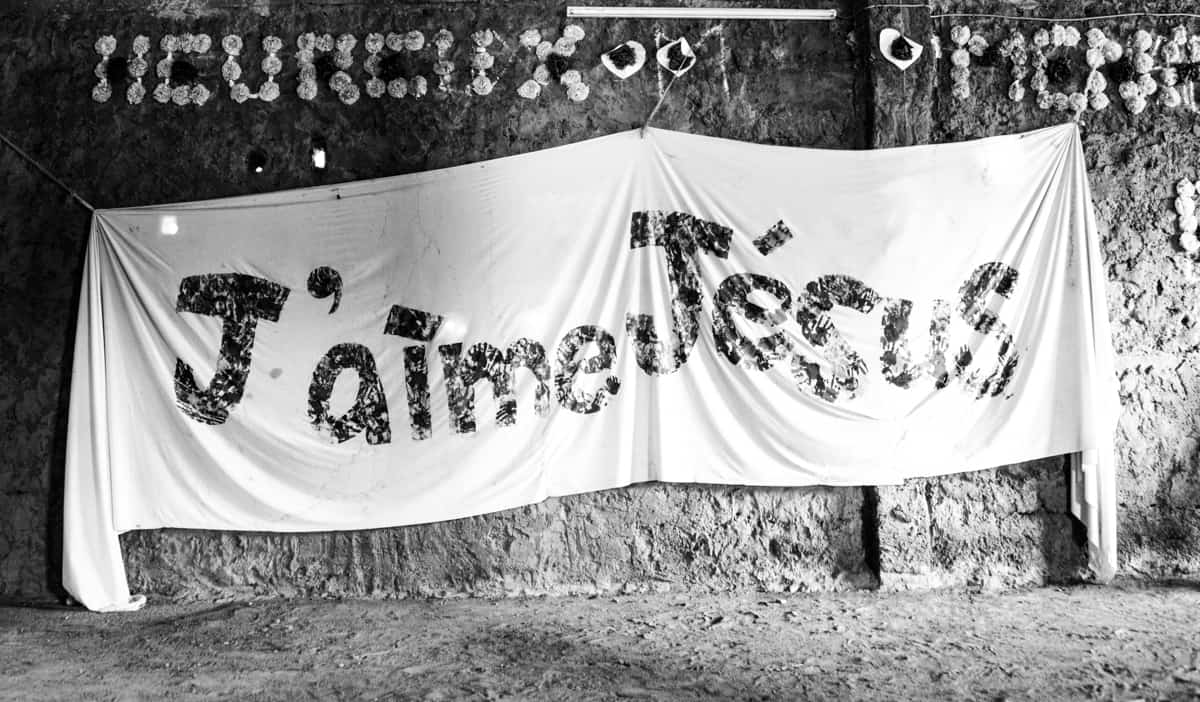 A giant cloth banner, sign reads j'aime Jésus, French for I love Jesus. It is hanging on a mud wall.