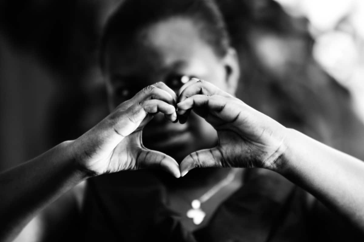 a child making a heart shape with their hands