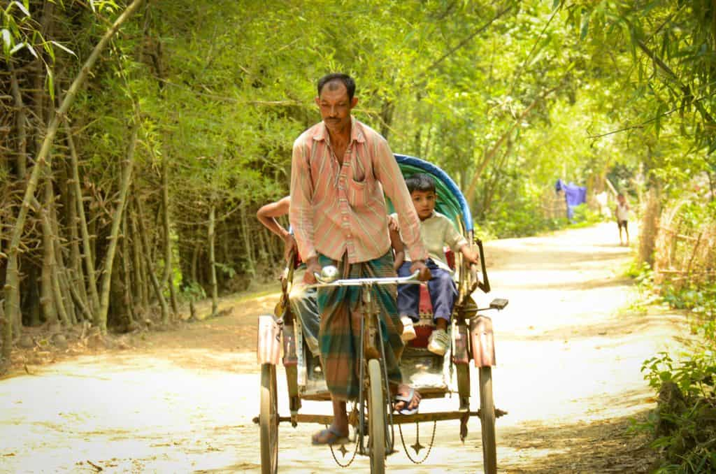 A man drives a rickshaw with children riding on it