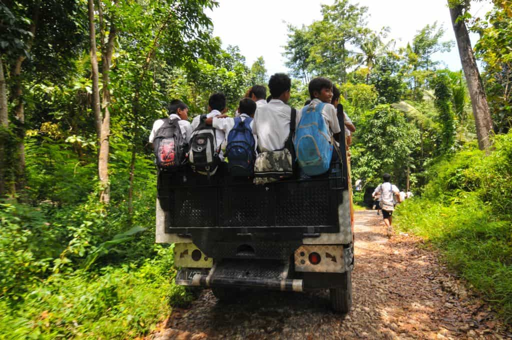 Schoolchildren wearing backpacks ride on the back of a truck down a dirt road in a rural area