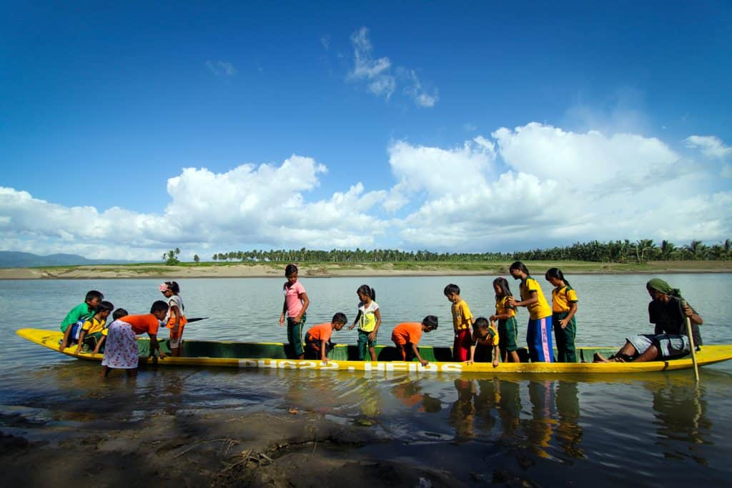 Children ride on a canoe made from a hollowed-out coconut tree. Some are standing and some are sitting.