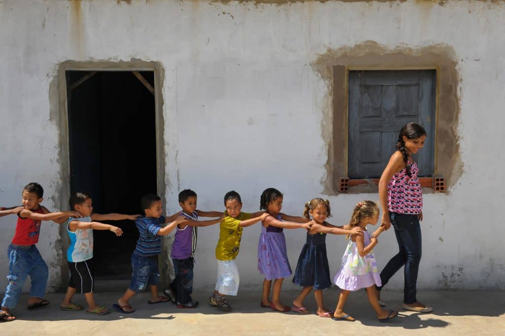 Children line up with their hands on each other's shoulders in single file, following an adult
