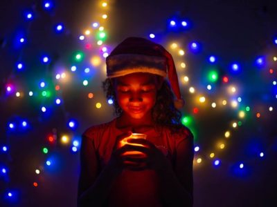 A girl in Brazil wears a Santa hat. She is smiling down at a candle. The room is dimly lit, and Christmas lights sparkle behind her.