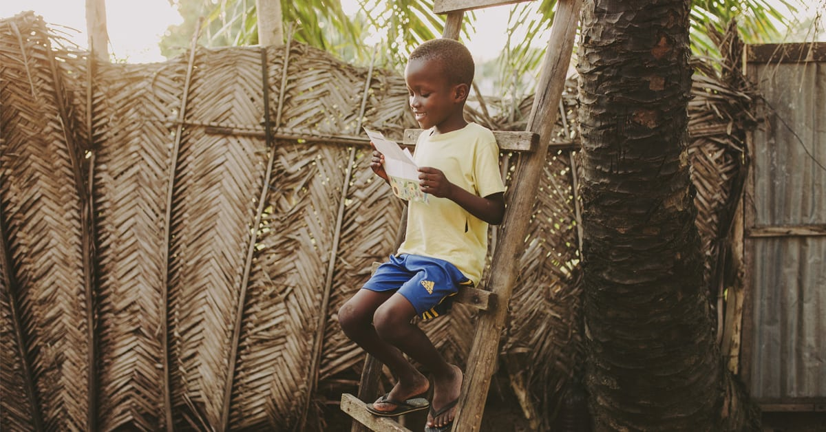 Young boy in a yellow shirt sitting on a step ladder reading a letter