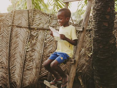 little boy sitting on ladder reading a letter
