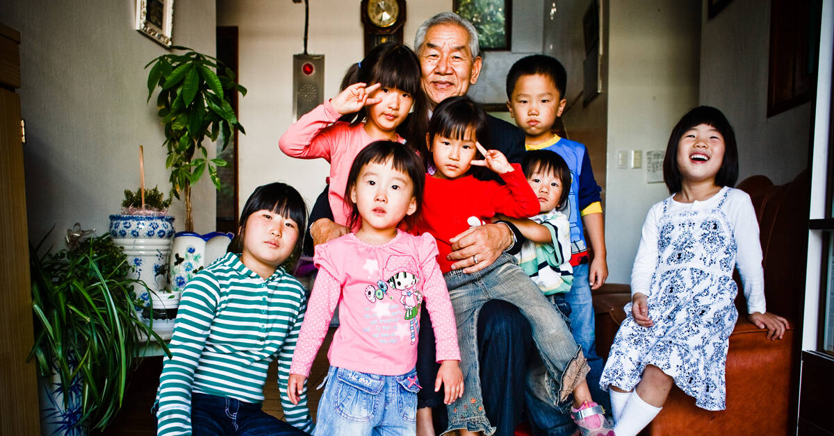 older gentleman surrounded by seven children
