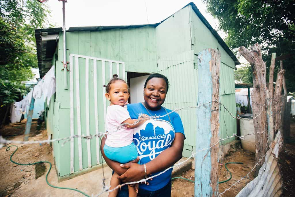 A smiling mother wearing a Royals T-shirt holds a small girl child. They are standing outside a pastel green structure where they live