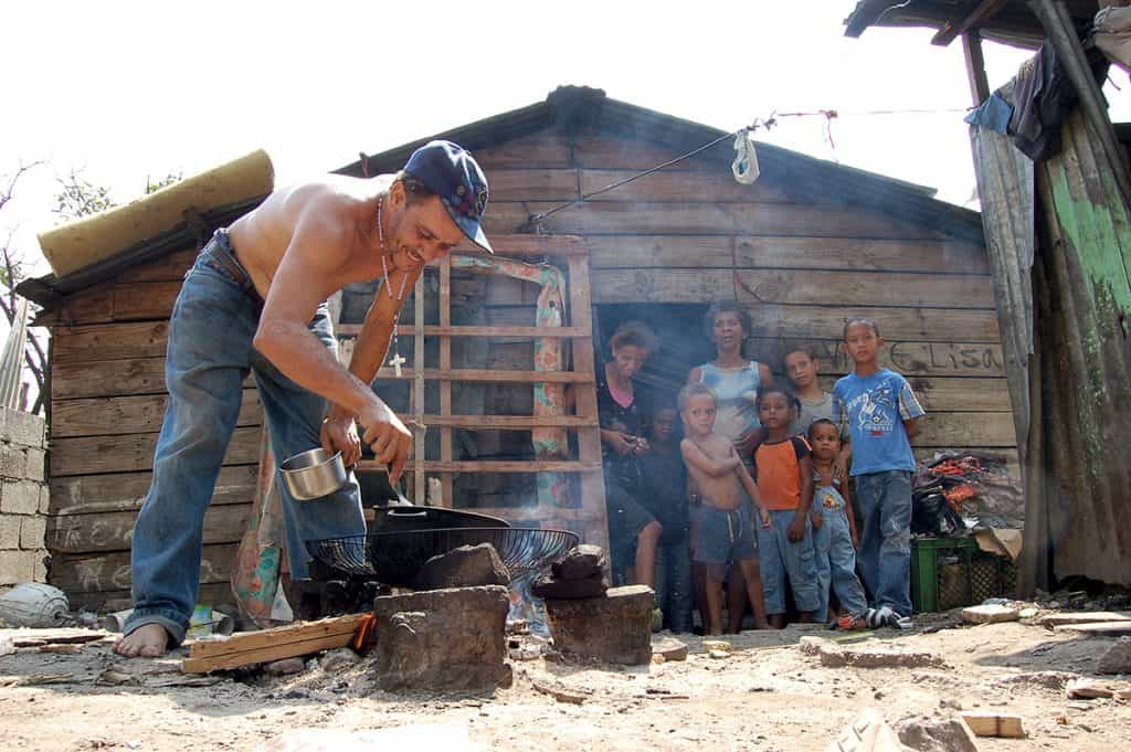 A father cooks for his family outside their tiny home in the Dominican Republic