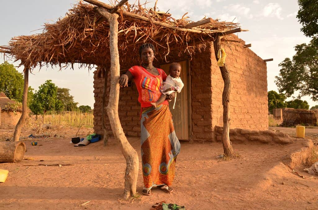 A mother holds her child outside their tiny home in Burkina Faso