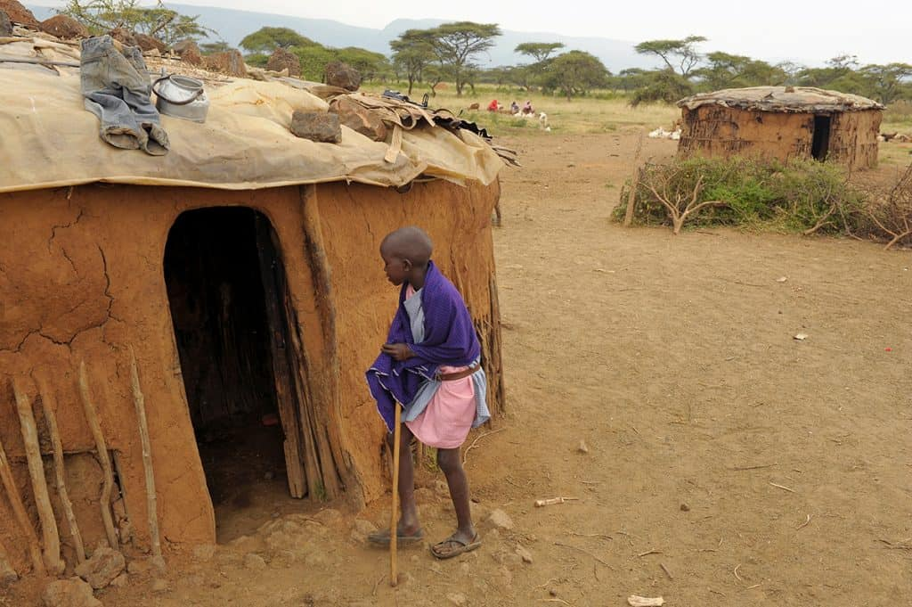 A Maasai boy in Kenya gets ready to enter a tiny home made of mud.