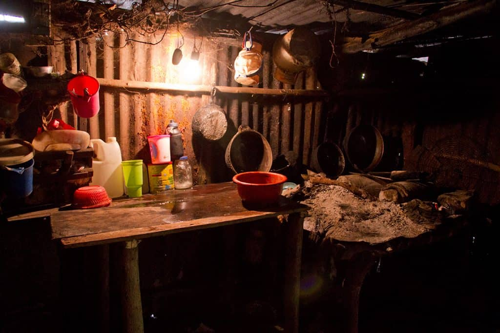 In this tiny kitchen, pots and pans hang from the roof and tin walls of a tiny home. A small wooden table is seen next to a pile of ashes where the family cooks.