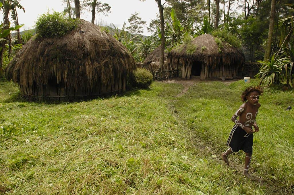 A boy in Indonesia running in the grass outside his tiny home, made of wooden slats and thatched roof.