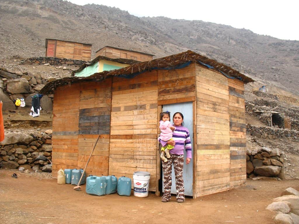 A mother holds a young girl. They are standing outside a small wooden home in Peru. Mountains are seen in the background.