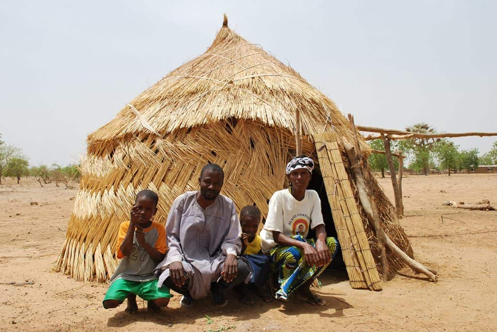 A family, a father and mother with two children, sit outside their home in Burkina Faso, which is made of woven reeds. It is light tan in color.