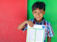 smiling boy holding a letter from sponsor