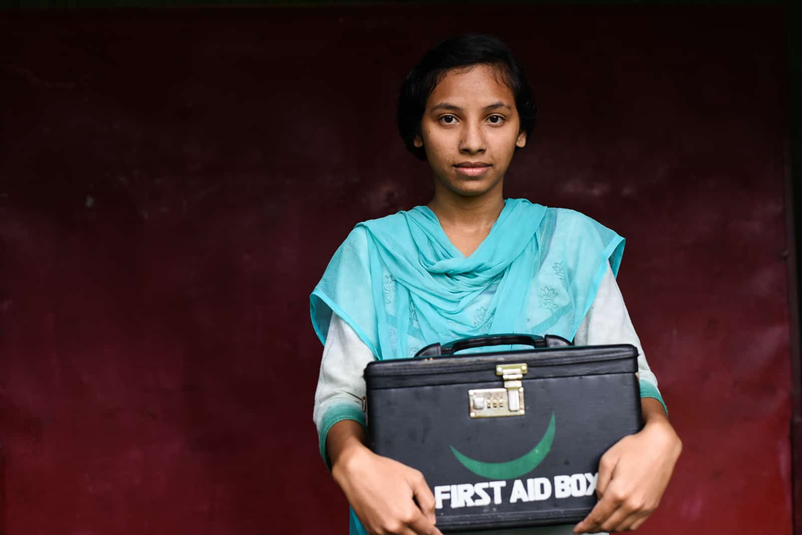 A teenage girl holds a medical kit