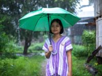 A girl in Thailand stands under an umbrella in the rain