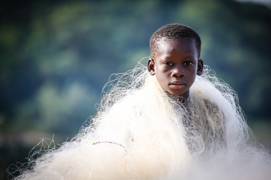 A boy with a net wrapped around his shoulders