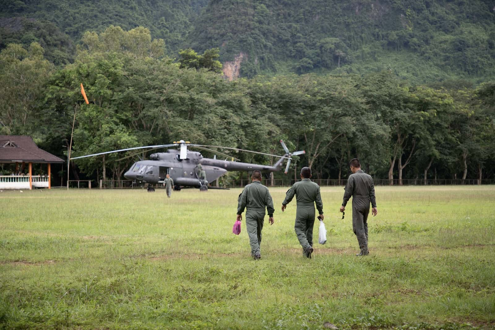 three military men walking towards helicopter