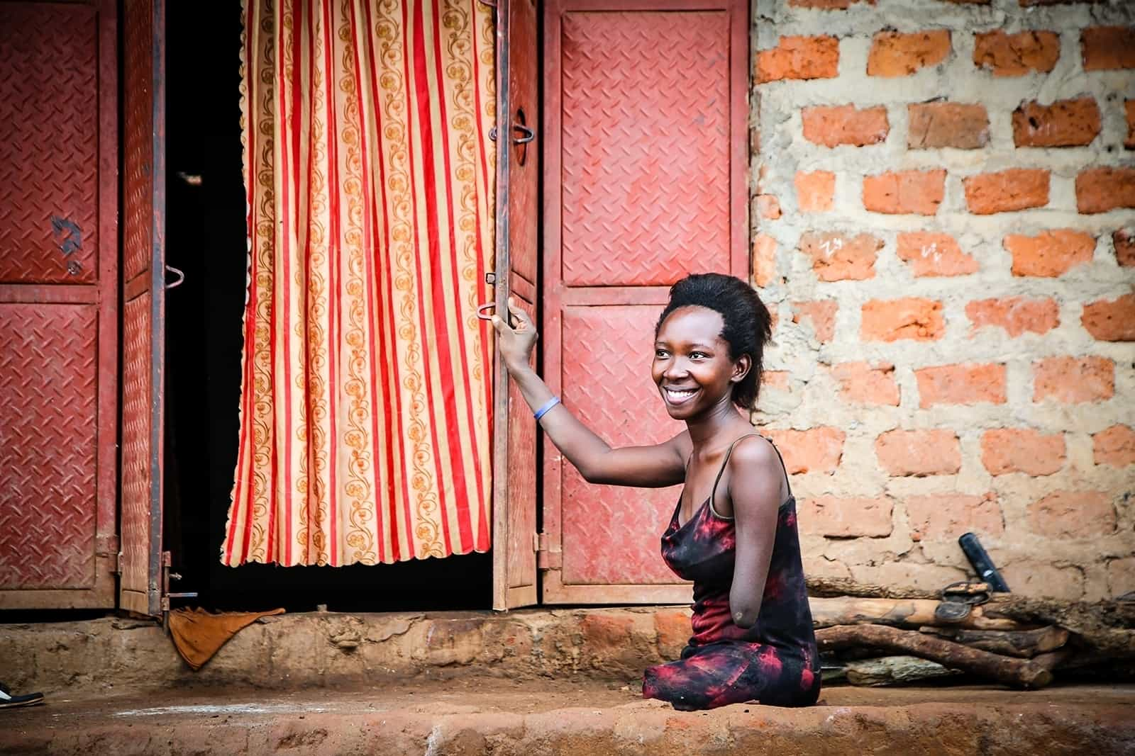 Grace outside her home in Uganda