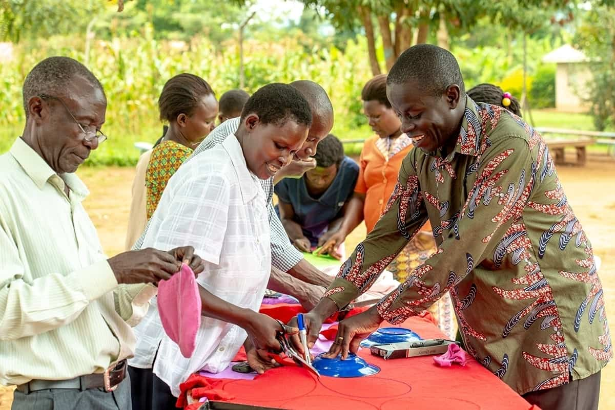 A group of people stand around a table making reusable sanitary pads.