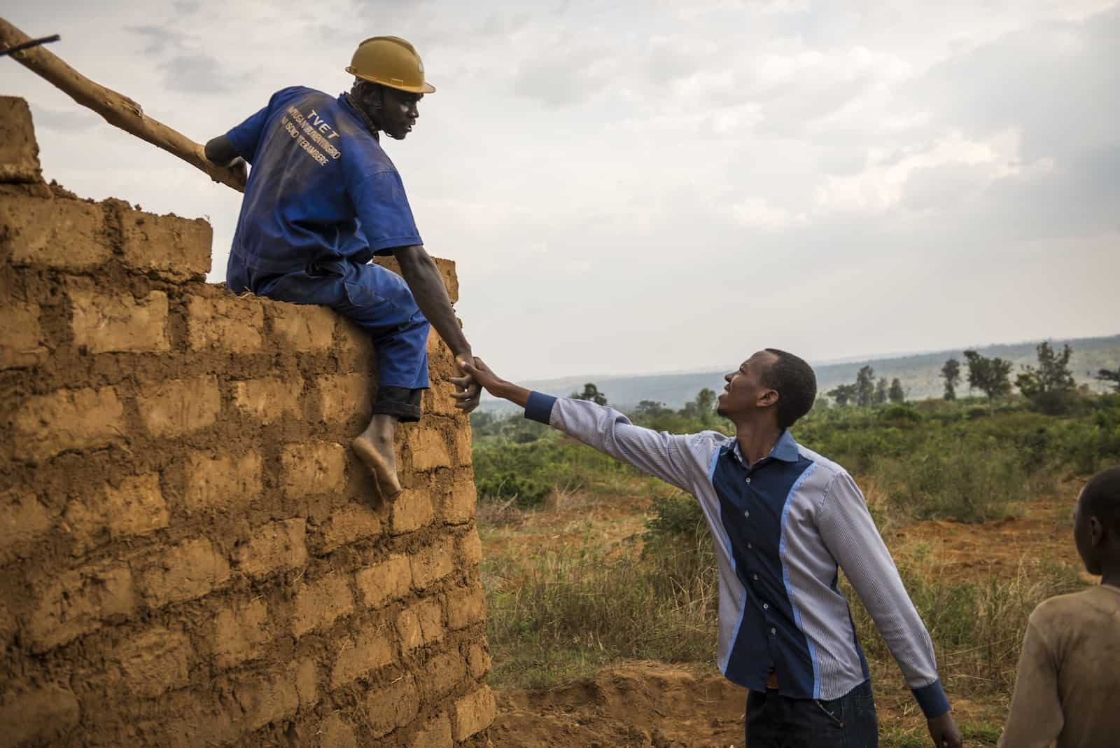 A man wearing a blue shirt reaches up and shakes the hand of a man sitting on a partially built brick wall. The man on the wall wears a hart hat and work clothes and looks down at the other man.