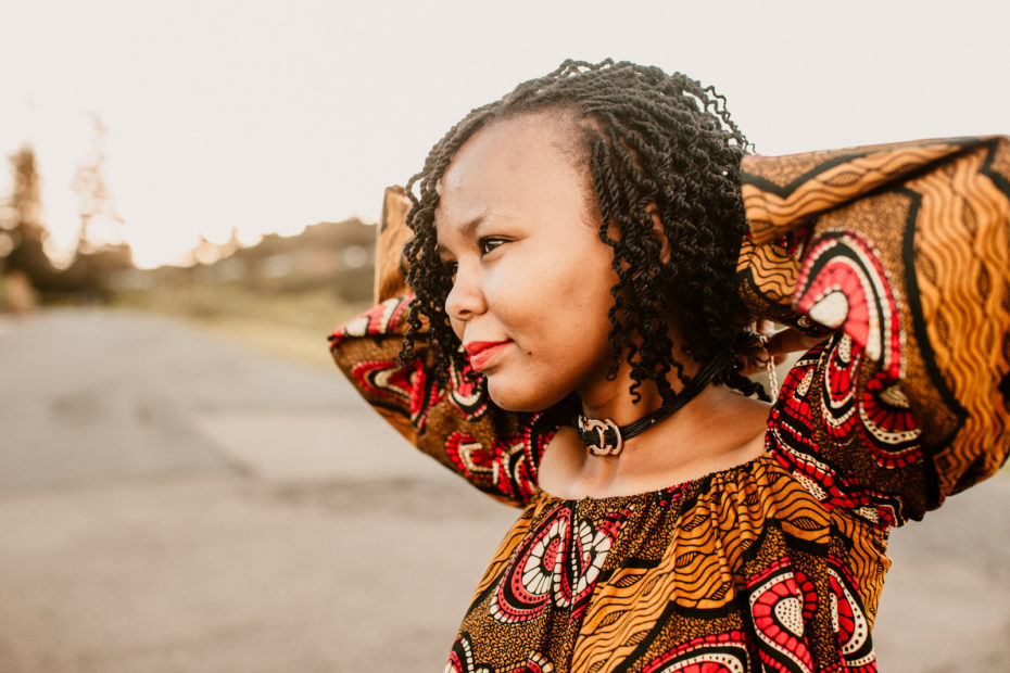 Christine stands with her arms behind her head, wearing an African-style dress and looking into the distance