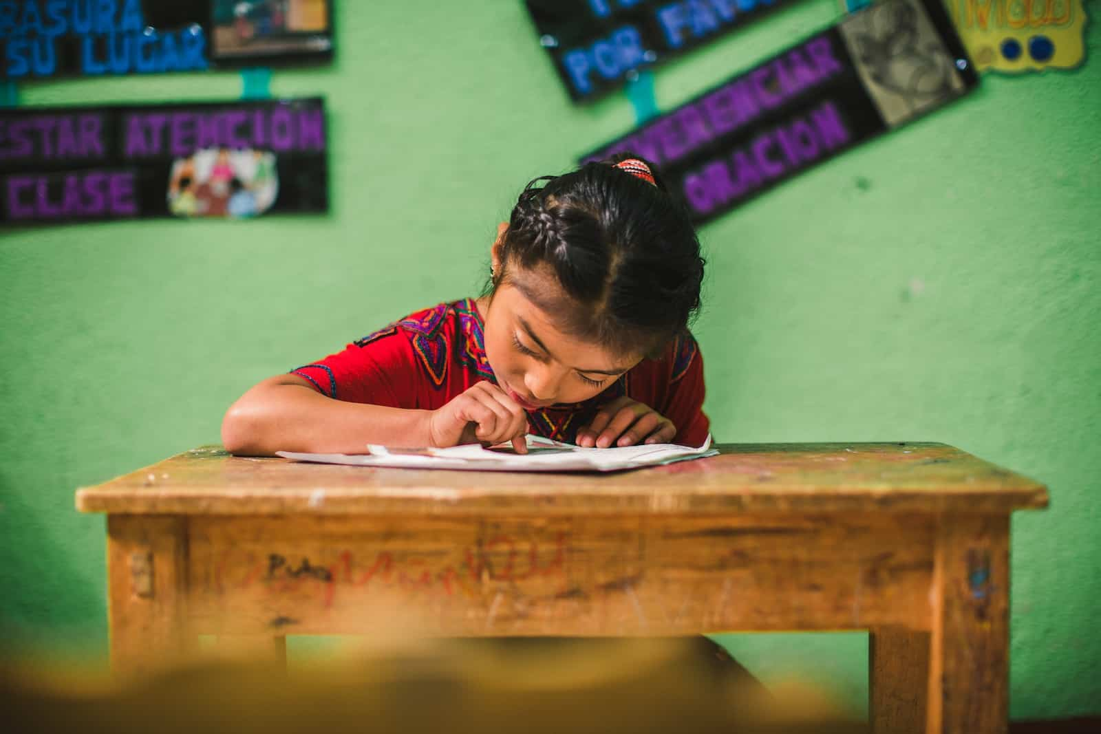 A girl from Guatemala in a red shirt with her hair pulled back sits at a wooden school desk, reading a letter. She is in front of a green wall.