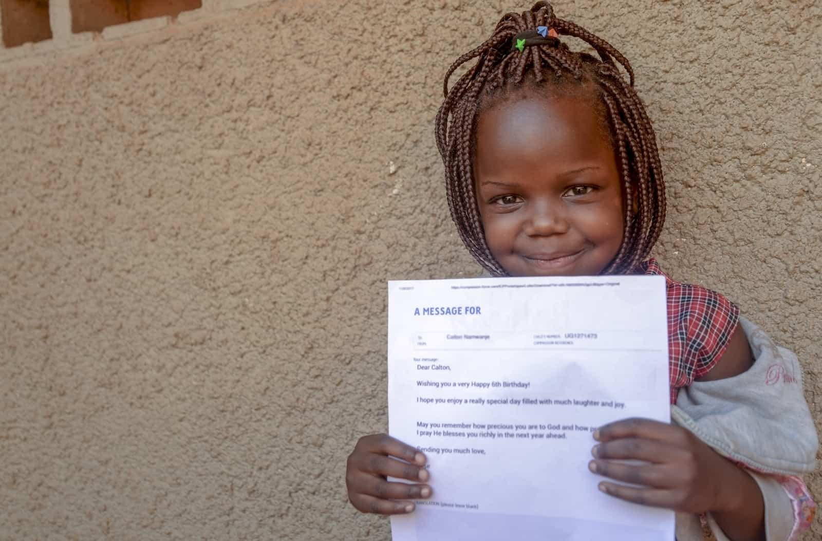 A young girl from Uganda with her hair in braids and a checkered shirt holds a letter in front of her and smiles.