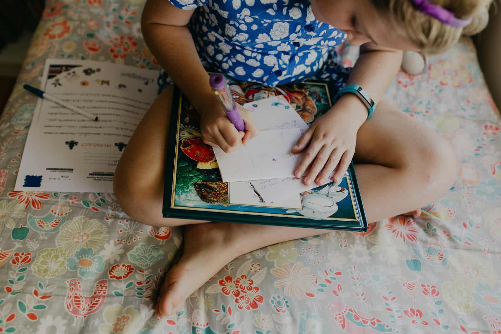 A girl with blonde hair and a blue dress on sits on her bed, legs crossed, writing a letter to the child she sponsors.