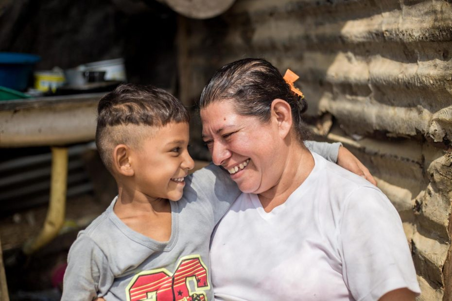 A woman stands smiling with her son in their kitchen where they have been feeding people fleeing Venezuela's economic crisis