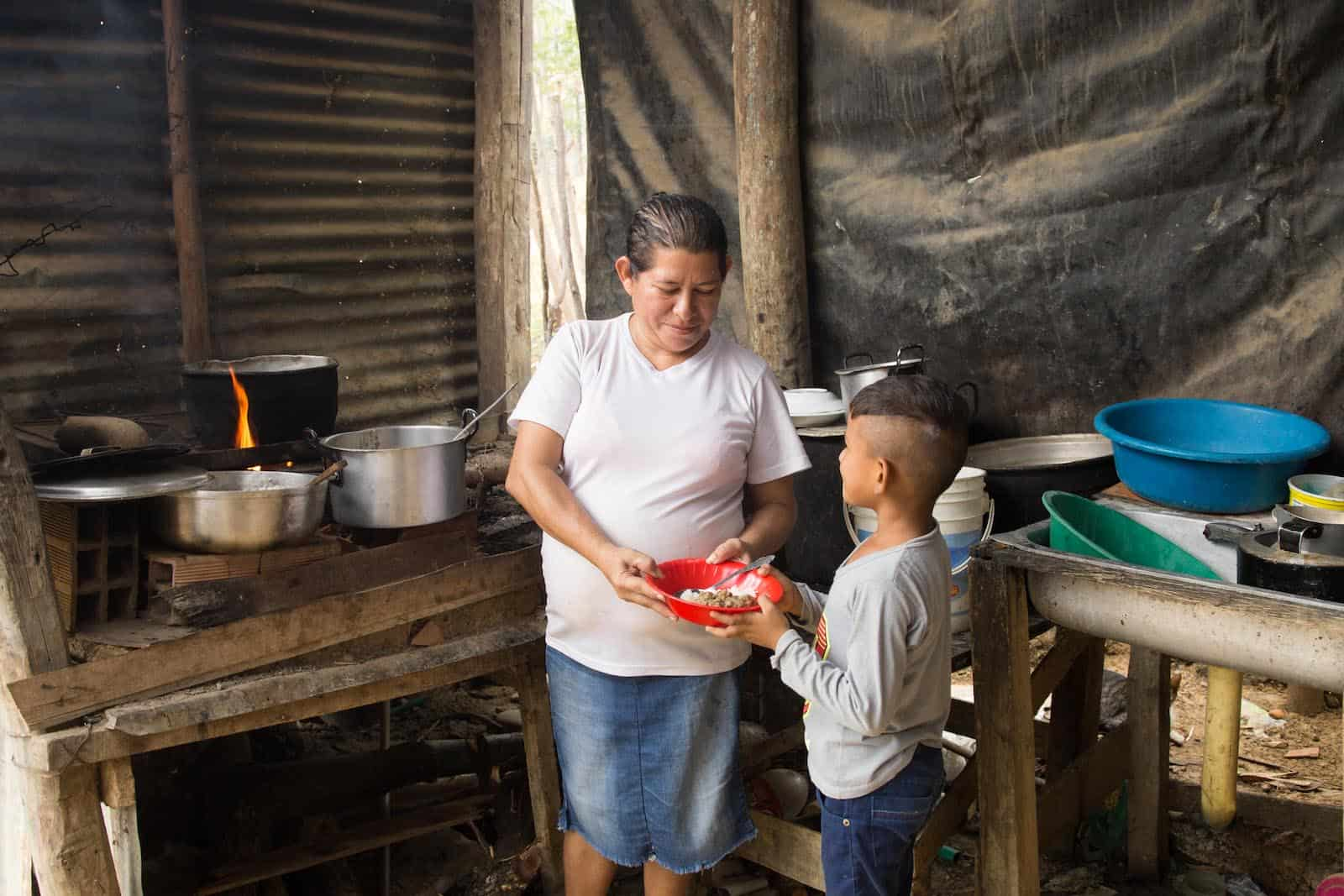 A woman stands in a kitchen handing a bowl of food to a boy.