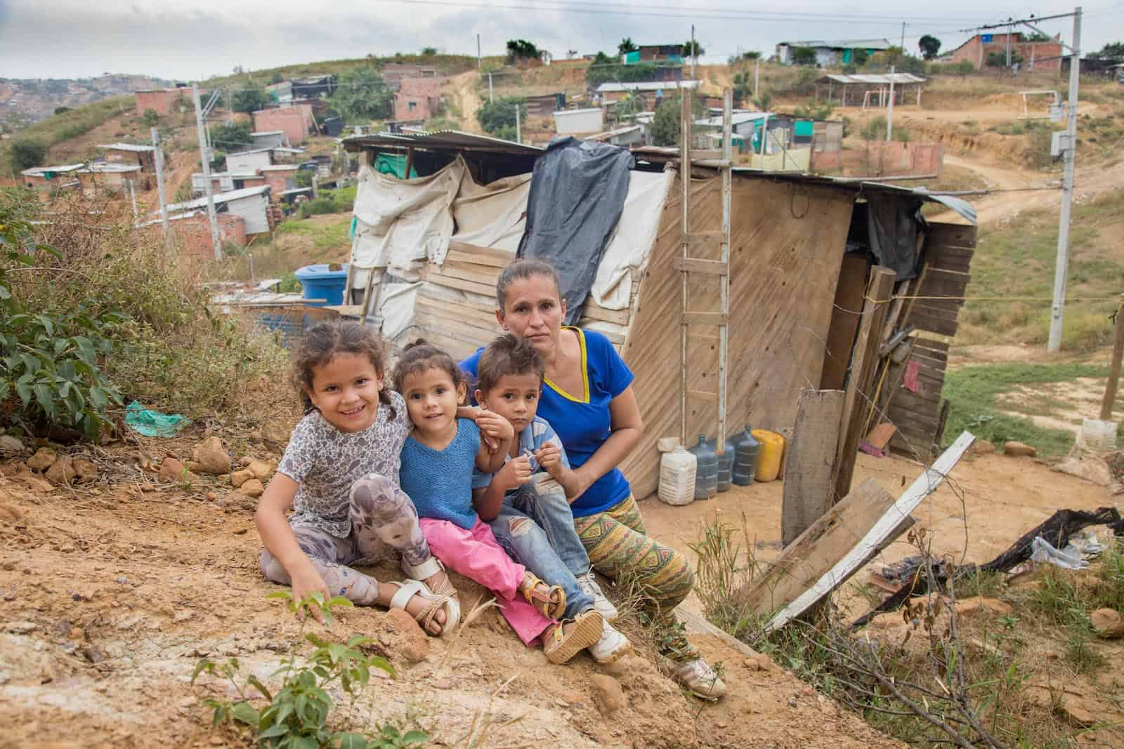 A woman and three children sit outside of a one-room home made of wood and plastic tarps where they are housing people who have left Venezuela after the political crisis.