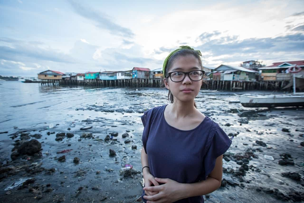 A girl wearing glasses and a blue shirt clasps her hands in front of her and looks to the side, standing in front of a waterway with homes on stilts in the background.