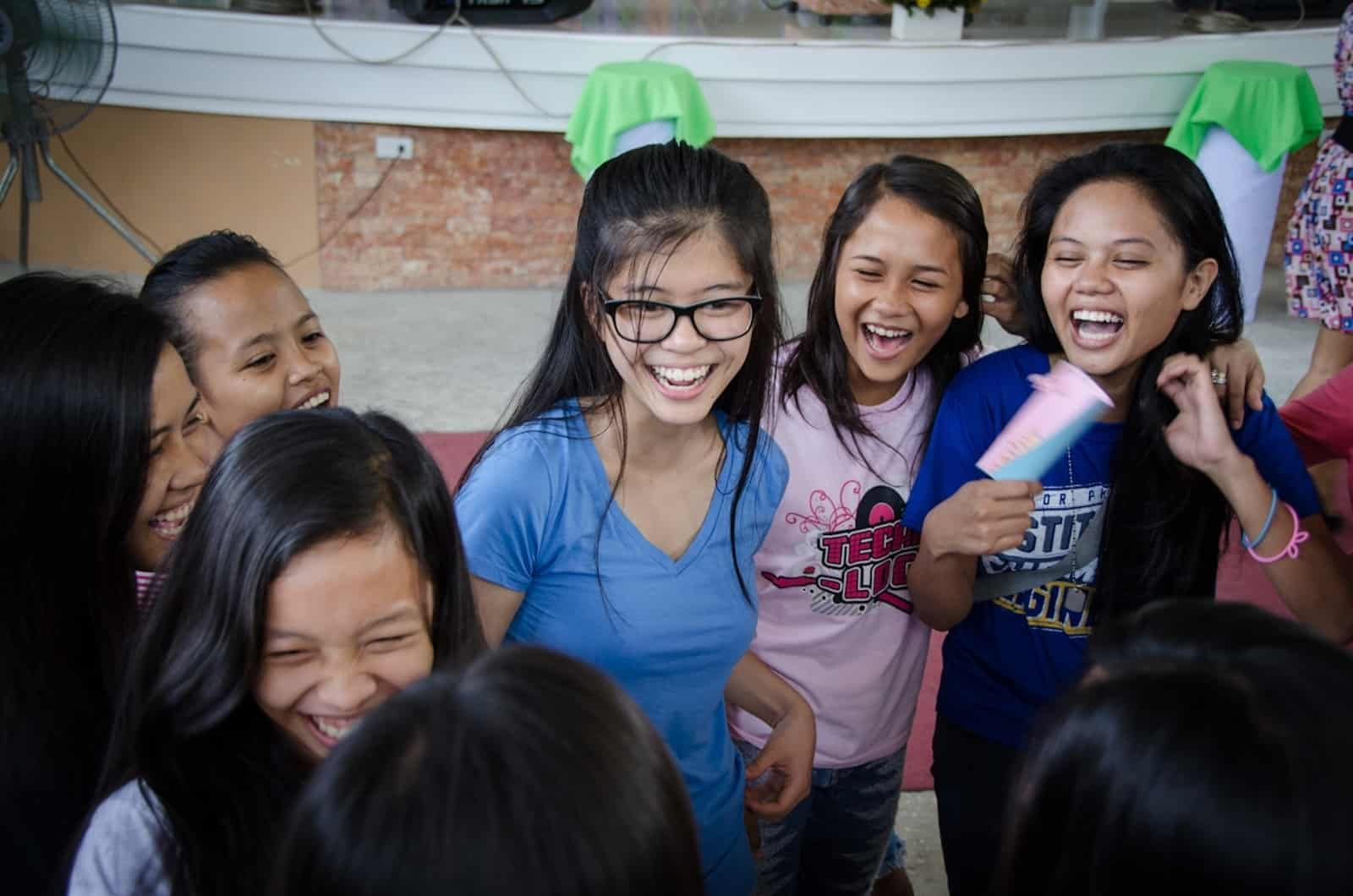 A group of girls smiles and laughs, standing inside a church.