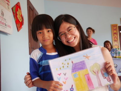 A young woman with glasses on puts her arm around a girl holding a drawing of a house.