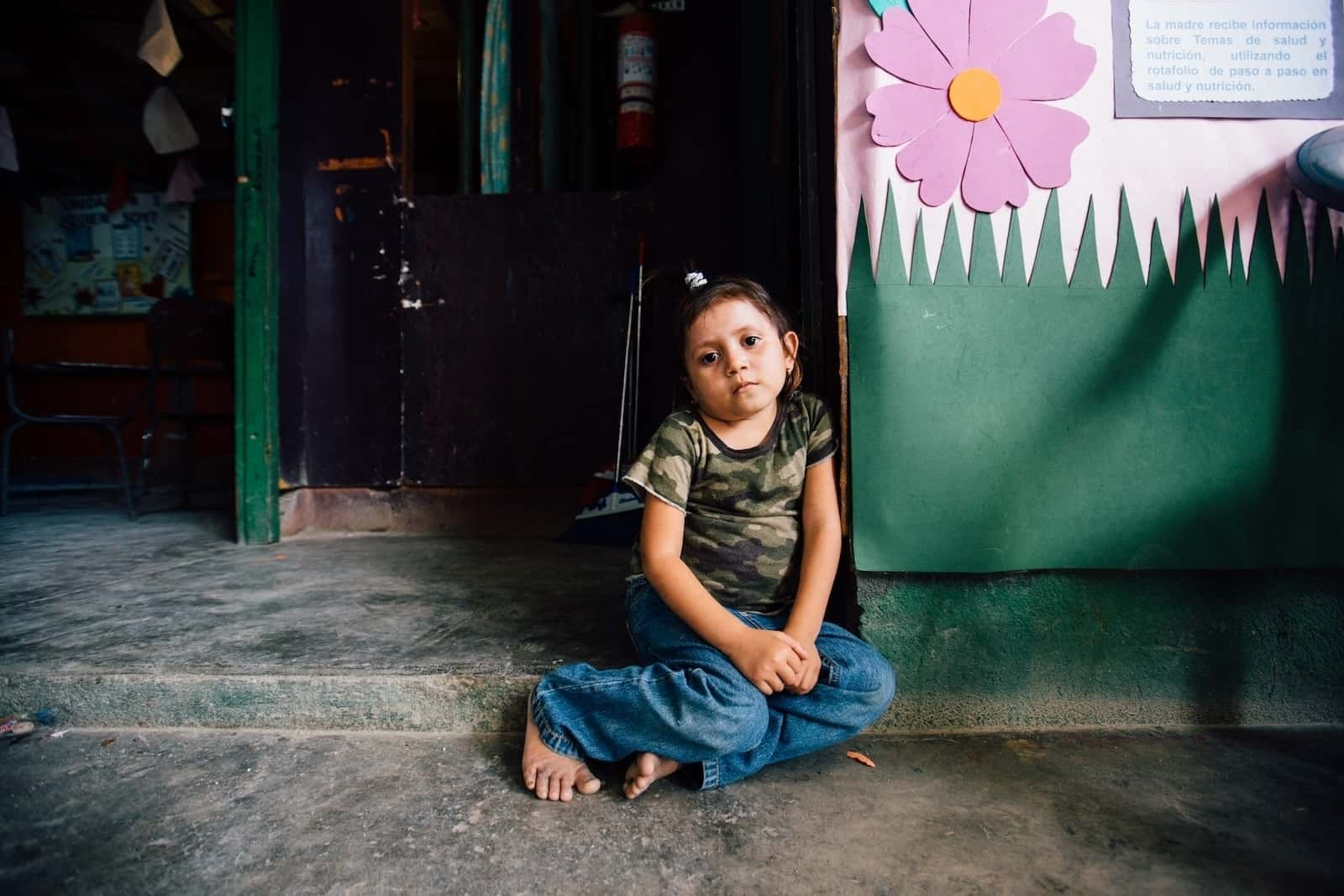 A little girl wearing a camouflage shirt, jeans and bare feet, sits on a concrete step, looking sad.