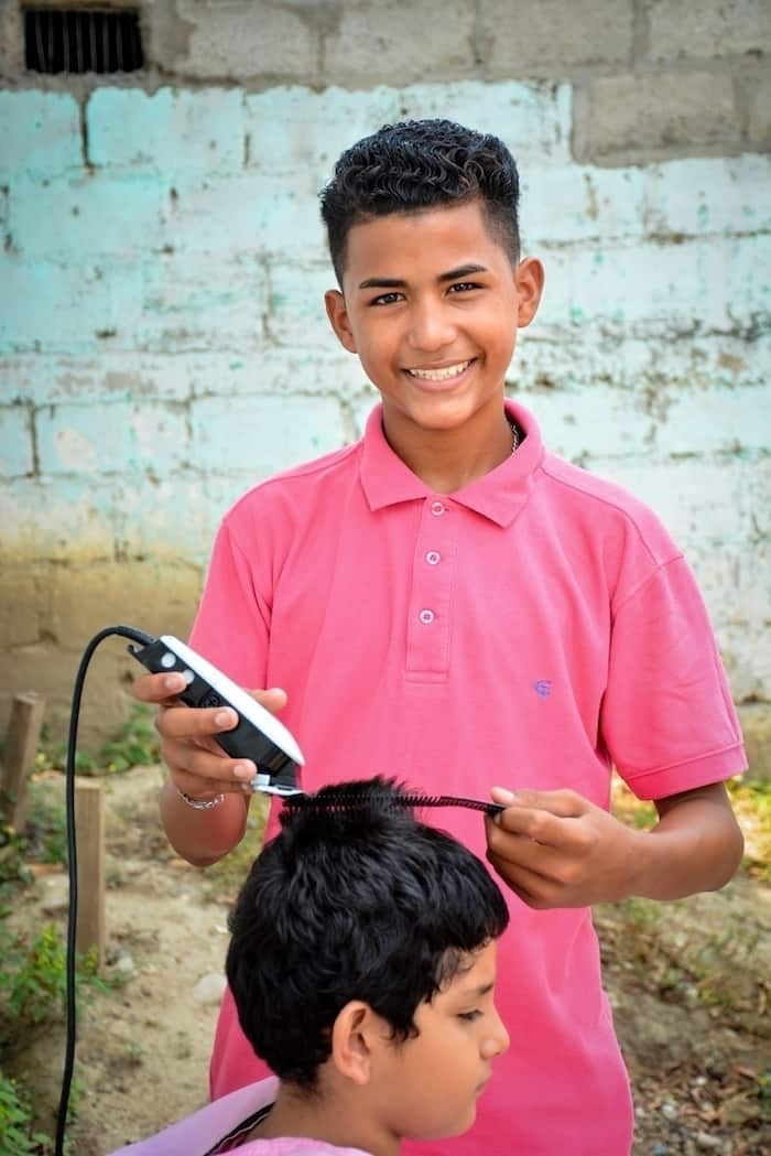 A boy wearing a pink shirt stands, smiling, cutting a boy's hair using clippers and a comb. They are in front of a light green brick wall.