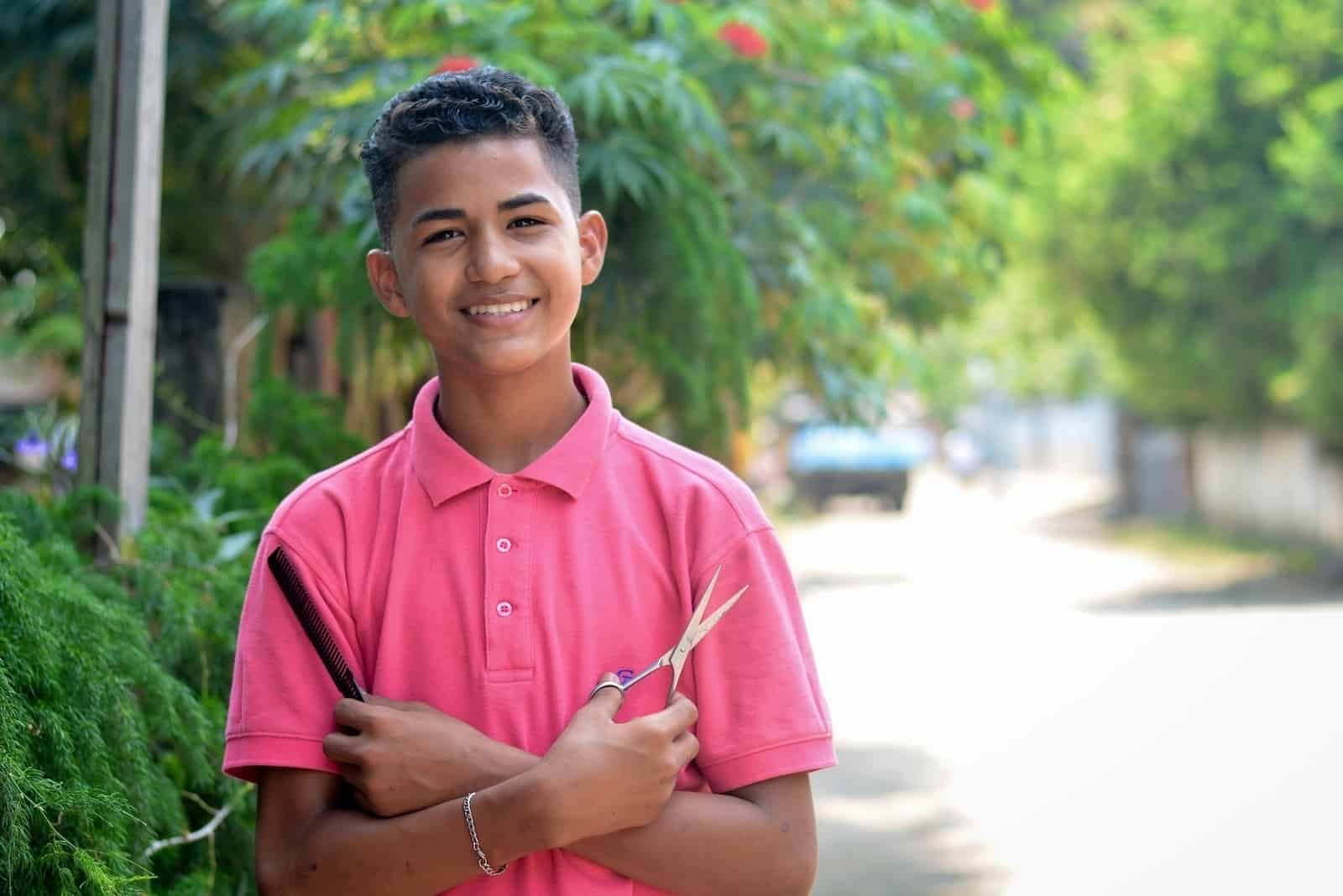 A boy wearing a pink shirt stands, smiling, with his arms crossed holding scissors in one hand and a comb in the other, standing on a street.