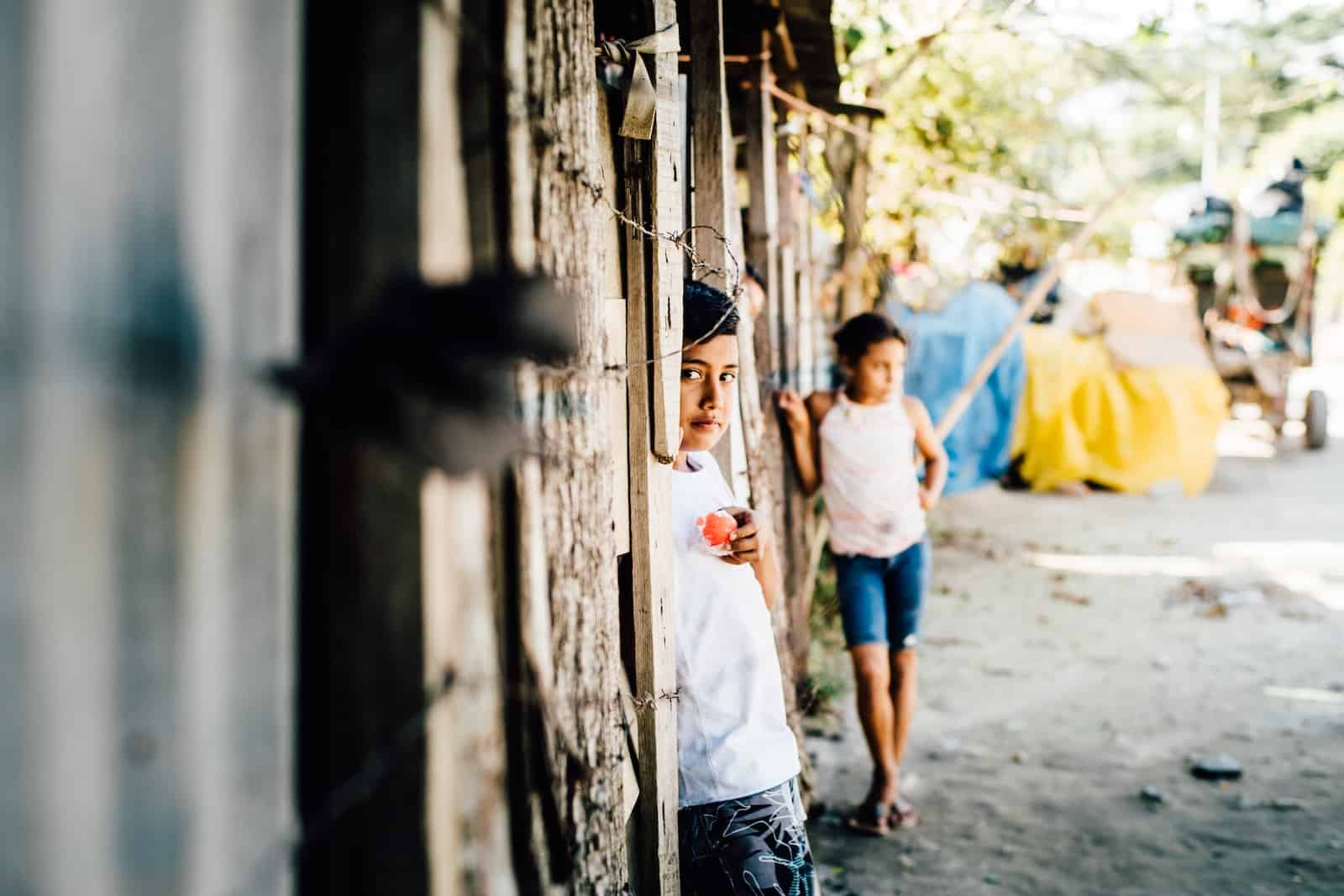 A boy stands in a wooden doorway with barbed wire fence wearing a white shirt. In the background is a girl and a dirt road.