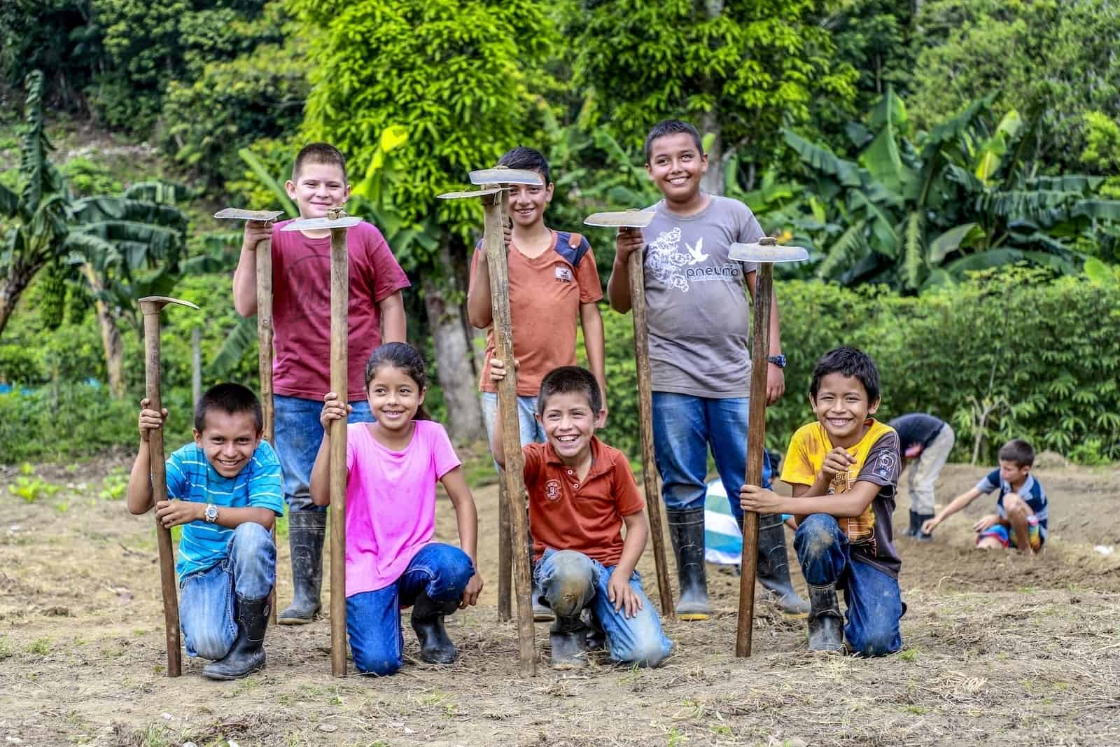 A group of seven children smile at the camera. Three are standing and three are crouching in a field, all holding hoes.